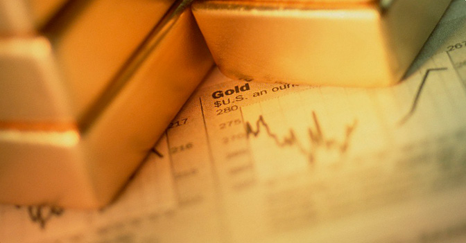 Bars of Gold Stacked on Stock Market Report --- Image by © Roman Konopka/First Light/Corbis